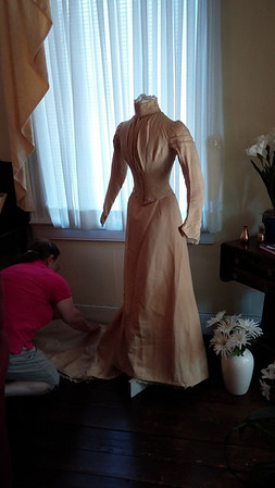 Re-enactor and master seamstress, Connie Clowers, prepares the 1892 Holladay wedding dress on the form.